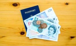 USA-pass och brittpengar på en tabell Royaltyfri Bild