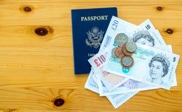 USA-pass och brittpengar på en tabell Arkivbilder
