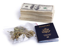 Drug Trafficking Pays Well. A USA passport, a zip-lock plastic bag containing marijuna buds and a large stack of 100 US dollar money notes isolated on white Stock Photo