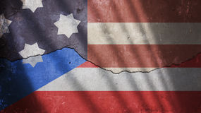 Usa and Puerto Rico Flag on a Cracked Wall with Gate Shadow Royalty Free Stock Images