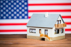 Usa realty concept. House against american flag Stock Photos