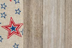 USA red and blue stars burlap ribbon on weathered wood backgroun Stock Images