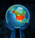 USA on Earth in hands. USA in red on globe held in hands in space. 3D illustration stock photo