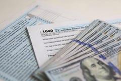 USA-skattform 1040 med nya 100 US dollarräkningar Arkivbild