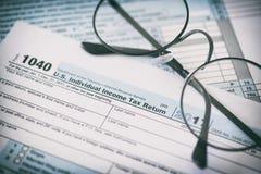 USA-skattform och exponeringsglas bakgrundsbegreppet bantar guld- äggfinans arkivfoto