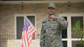 USA soldier showing keys from house, mortgage help from veterans organization. Stock footage stock video footage