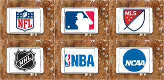 Usa sports logos and icons. Collection of logos and vector of most popular usa sports leagues on white tablet on rusty wooden background. leagues like nfl, mls Royalty Free Stock Image