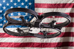 USA Spy drone. A small spy quad copter drone flying over a wrinkled usa flag stock photo