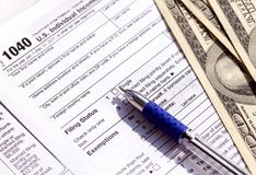 US 1040 Tax form, pen and dollar bills. Concept of tax refund stock photos