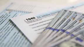 USA Tax Form 1040 with 100 US dollar bills. Business concept Stock Images