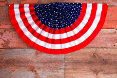 USA 4th of July patriotic rosette. 4th of July patriotic rosette in the stars and stripes of the USA National flag to celebrate Independence Day lying on rustic Stock Images