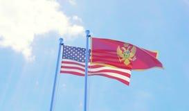 USA und Montenegro-Flaggen, die gegen blauen Himmel wellenartig bewegen Lizenzfreie Stockfotos