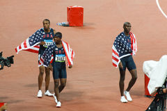 USA victory Lap Mens 400m Hurdles. BEIJING, CHINA - AUGUST 16, 2008: Angelo Taylor, Kerron Clement, and Bershawn Jackson take a victory lap after USA sweeps men' Stock Photos