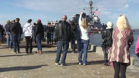 USA Virgina Norfolk, November 2015, medium shot. US Marine Soldiers stand on the ship deck. A group of civilian look away the driving ship stock video