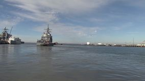 USA Virgina Norfolk, November 2015, wide shot USS. The USS Anzio drive out of the harbour with the help of two tugboats stock video footage