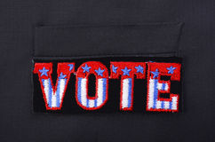 USA Vote Badge on suit pocket. Closeup of USA vote badge on black suit jacket pocket Stock Image