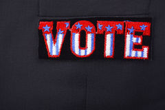 USA Vote Badge on suit pocket. Closeup of USA vote badge on black suit jacket pocket, with additional copy space Royalty Free Stock Photos
