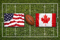 USA vs. Canada flags on rugby field. USA vs. Canada flags on green rugby field royalty free stock photos