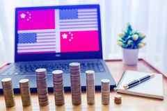 USA vs China flag in laptop screen on wooden table. Gold and silver coins are front of laptop and notebook with pen. The concept of trade war between America stock photos