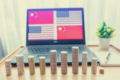 USA vs China flag in laptop screen on wooden table. Gold and silver coins are front of laptop and notebook with pen. The concept of trade war between America stock image
