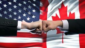 USA vs Kanada konflikt, stosunek międzynarodowy kryzys, pięści na chorągwianym tle zbiory wideo