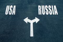 USA vs RUSSIA choice concept. Two direction arrows on asphalt Stock Images