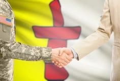 USA wojskowy w jednolitym i cywilnym mężczyzna w kostiumu chwiania rękach z pewną Kanadyjskiej prowinci flaga na tle - Nunavut zdjęcia royalty free