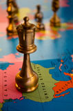 USA world chess queen. A queen chess piece on the nation of USA, with the other pieces in the world in the background Stock Photography