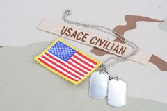 USACE CIVILAN branch tape with dog tags and flag patch on desert camouflage uniform. USACE CIVILAN branch tape with dog tags  and flag patch on desert camouflage Stock Photos