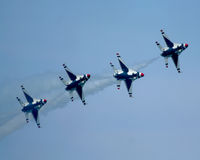 USAF Thunderbirds. Line of four F-16 planes with exhaust trails behind them, members of the Thunderbirds demonstration team of the United States Air Force Royalty Free Stock Image