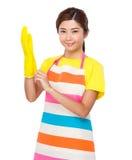Usage asiatique de femme au foyer avec les gants en plastique photo libre de droits