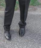 Usage masculin de chaussure de noir d'affaires de jambes sur le plancher Images stock