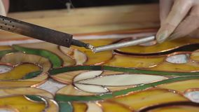Usage of soldering iron on a colored glass. Close up shot of soldering iron usage on a stained glass in a workshop. Tracing the ornament stock video