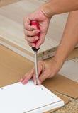 Usando a chave de fenda Assembling Wooden Furniture foto de stock royalty free