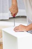 Usando a chave de fenda Assembling Wooden Furniture imagem de stock