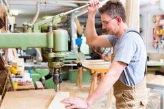 Usando del carpentiere elettrico perfora dentro la carpenteria fotografie stock