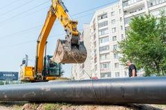 Usando dell'escavatore come gru per l'innalzamento del tubo Fotografie Stock