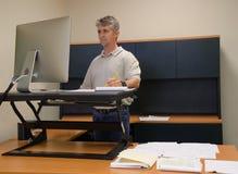Usando dell'uomo sta sullo scrittorio in ufficio per i buona salute immagini stock libere da diritti
