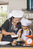 Usando della figlia e della madre sbatte per mescolare la farina di frumento e dell'uovo Fotografie Stock Libere da Diritti