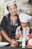 Usando della figlia e della madre sbatte per mescolare la farina di frumento e dell'uovo Fotografia Stock