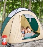usando della tenda del computer portatile delle coppie Fotografia Stock