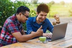 Usando di due uomini allegro e lavorare al computer portatile immagini stock libere da diritti