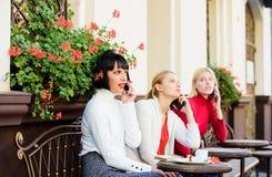 Usando dispositivos digitais Terraço do café das mulheres do grupo Reuni?o da amizade O móbil dedicou-se Conversa??o m?vel Menina fotos de stock