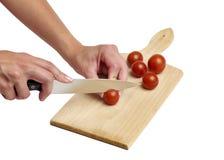Usando el cuchillo de cocina para cortar el tomate Imágenes de archivo libres de regalías
