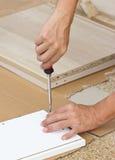 Usando el destornillador Assembling Wooden Furniture imagen de archivo libre de regalías