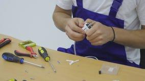Usando el destornillador para separe del enchufe eléctrico foto de archivo libre de regalías