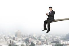 Usando el hombre de negocios del teléfono móvil que se sienta en el trampolín con los citys Foto de archivo libre de regalías
