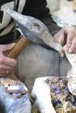 Usando el martillo para formar pedazos de la teja de mosaico imagen de archivo