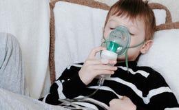 Usando el nebulizador y el inhalador para el tratamiento Muchacho con los ojos cloused que inhala a través de la máscara del inha Imagen de archivo