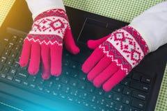 Usando el ordenador portátil en el invierno frío, femenino con los guantes encendido Foto de archivo